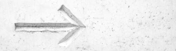 cropped image of an arrow etched into a wall