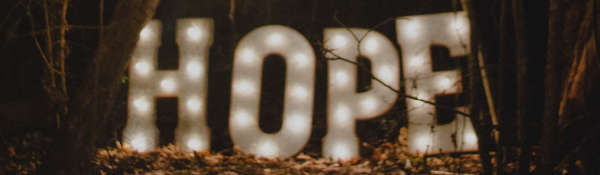 Image of neon lit letters spelling out HOPE, placed roughly on fallen leaves in a dark woodland