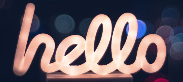 neon lettering of word 'hello' against dark background