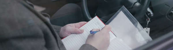 Image of person writing in a notepad inside a car